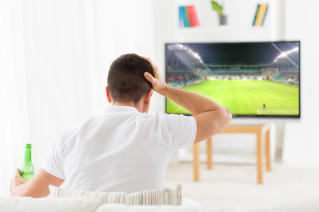 entertainment concept: leisure, technology, sport, entertainment and people concept - man with beer bottle watching football or soccer game on tv at home
