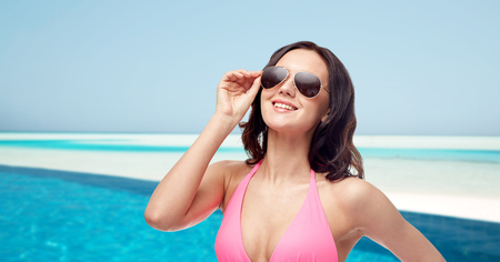 people, fashion, swimwear, summer and travel concept - happy young woman in sunglasses and pink bikini swimsuit over maldives beach with swimming pool background