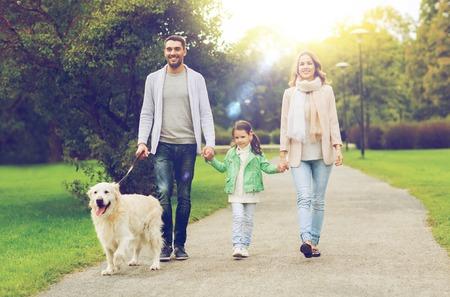 familia, mascotas, animales domésticos y las personas concepto - familia feliz con el perro labrador retriever caminando en el parque de verano