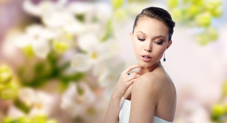 asian natural: beauty, jewelry, people and luxury concept - beautiful asian woman or bride with earring and finger ring over natural spring lilac blossom background