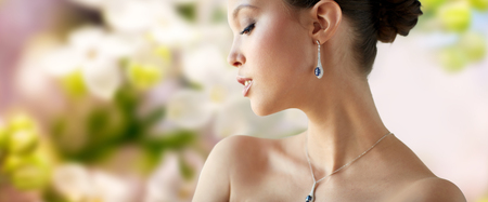 asian natural: beauty, jewelry, wedding accessories, people and luxury concept - beautiful asian woman or bride with earring and pendant over natural spring lilac blossom background