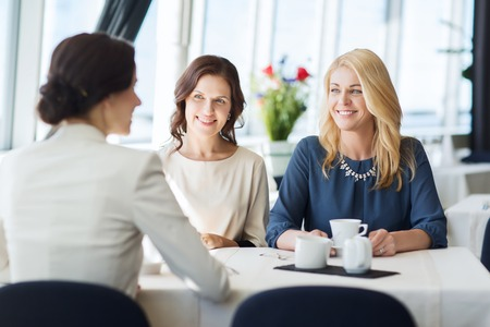 women coffee: people, communication and lifestyle concept - happy women drinking coffee and talking at restaurant Stock Photo