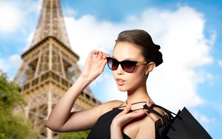 Verkoop, mode, tour, mensen en luxe concept - gelukkige mooie jonge vrouw in zwarte zonnebril met boodschappentassen over parijs eiffeltoren achtergrond