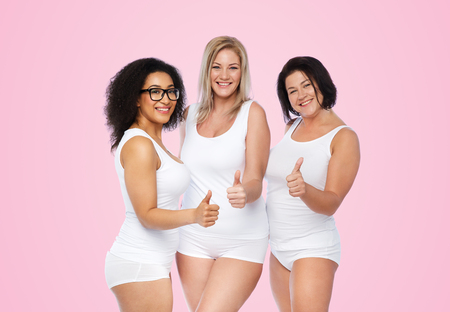 gesture, friendship, beauty, body positive and people concept - group of happy plus size women in white underwear showing thumbs up over pink background Stock Photo