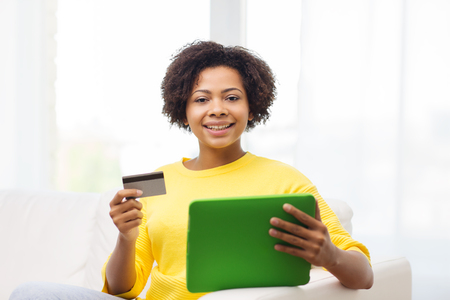 emoney: people, internet bank, online shopping, technology and e-money concept - happy african american young woman sitting on sofa with tablet pc computer and credit card at home
