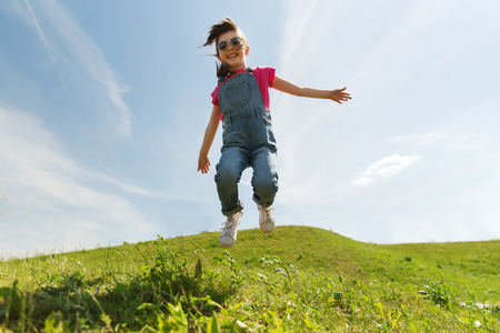 summer, childhood, leisure and people concept - happy little girl jumping high over green field and blue sky outdoors Stock Photo