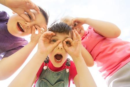 verano, la infancia, el ocio y el concepto de la gente - grupo de niños felices que se divierten al aire libre y que hacen caras