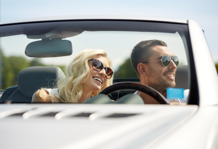 road trip, travel, dating, couple and people concept - happy man and woman driving in cabriolet car outdoors Stock Photo - 62560359