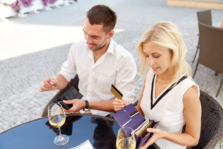 paying: date, people, payment and finances concept - happy couple with wallet and wine glasses paying bill at restaurant