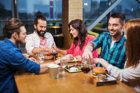per il tempo libero, mangiare, cibo, le persone e le vacanze concetto - sorridente amici a cena e degustazione l'altro piatto al ristorante