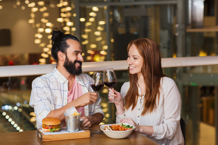 middle eastern families: leisure, eating, food and drinks, people and holidays concept - smiling couple having dinner and drinking red wine at restaurant Stock Photo
