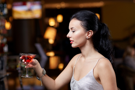 latin girls: people, party, nightlife, drink and holidays concept - glamorous woman with cocktail at night club or bar