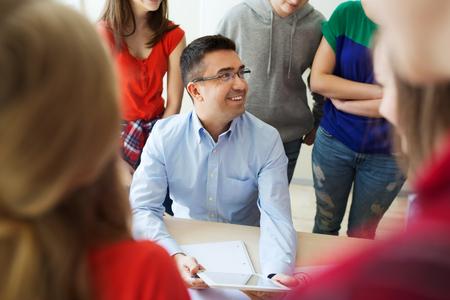 educadores: la educación, el aprendizaje, la enseñanza, la tecnología y el concepto de personas - grupo de estudiantes y profesores con el equipo de PC tableta que hablan en la escuela Foto de archivo