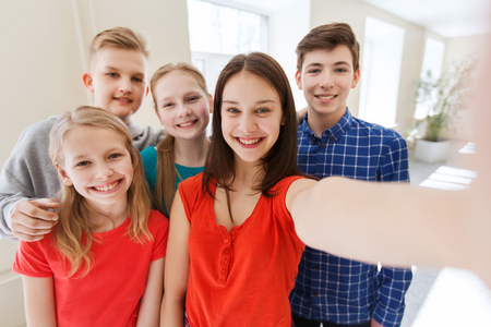 school teens: education, school, technology and people concept - group of happy smiling students taking picture with smartphone selfie stick in corridor