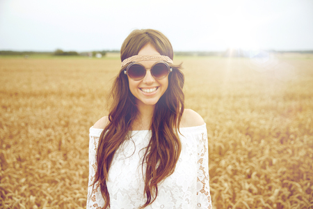woman in field: nature, summer, youth culture and people concept - smiling young hippie woman in sunglasses on cereal field Stock Photo