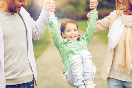 Familia, la felicidad, la niñez y la gente concepto - cerca de feliz madre, padre y niña caminando en el parque de verano y divertirse Foto de archivo - 62560462