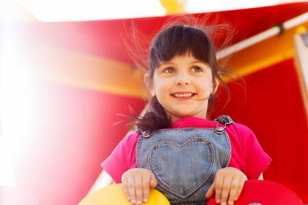 summer, childhood, leisure and people concept - happy little girl on playground climbing frame Stock Photo