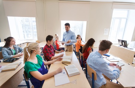 school exam: education, school, learning and people concept - group of students and teacher with test results in classroom