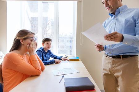 onderwijs, school, leren en mensen concept - groep studenten en docenten met de testresultaten in de klas
