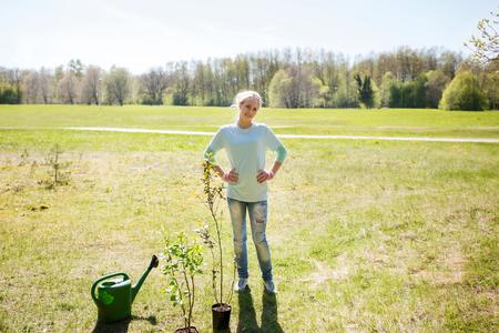 altruismo: la gente, el voluntariado y el medio ambiente concepto - mujer feliz joven voluntario al aire libre