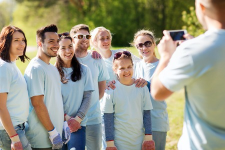group picture: volunteering, charity, people, teamwork and environment concept - group of happy volunteers taking picture by smartphone in park Stock Photo