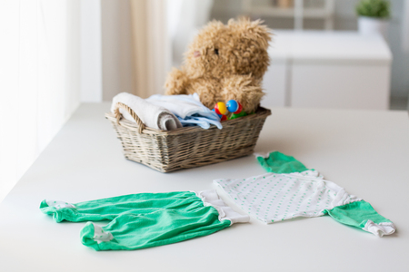 babyhood, motherhood, clothing and object concept - close up of baby clothes set and toys for newborn in basket at home Stock Photo