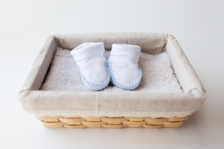 bootees: clothing, babyhood, motherhood and object concept - close up of white baby bootees for newborn boy on towel in basket Stock Photo