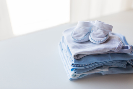 folded clothes: clothing, babyhood, motherhood and object concept - close up of baby bootees on pile of folded clothes for newborn boy