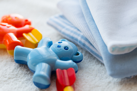 babyhood: babyhood, childhood, toys, clothing and object concept - close up of baby rattle and clothes for newborn boy on towel