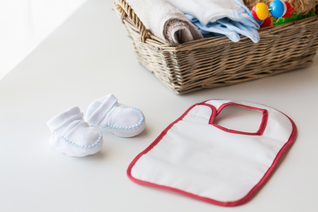 bootees: babyhood, childhood, motherhood and object concept - close up of white baby bootees, bib and newborn stuff in basket on table Stock Photo