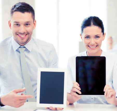 pcs: smiling business team showing tablet pcs in office Stock Photo