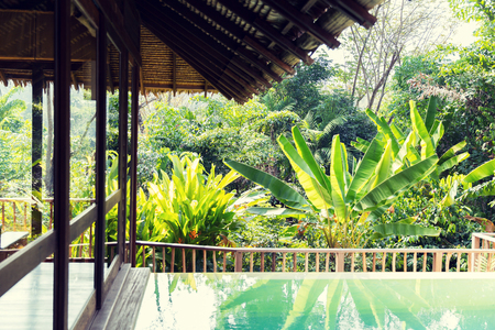 tropical garden: leisure, travel and tourism concept - swimming pool and bungalow at hotel resort
