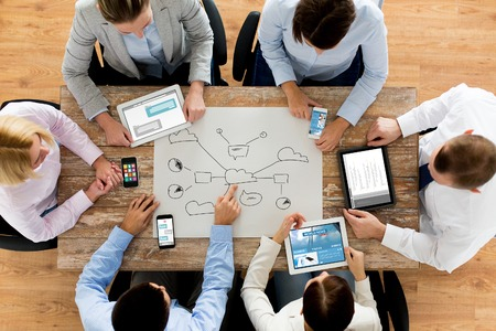 business, people, technology, cloud computing and team work concept - close up of creative team with smartphones and tablet pc computers sitting at table in office Stockfoto