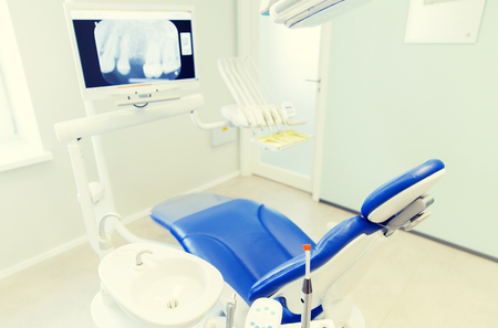 stomatological: dentistry, medicine, medical equipment and stomatology concept - interior of new modern dental clinic office with chair