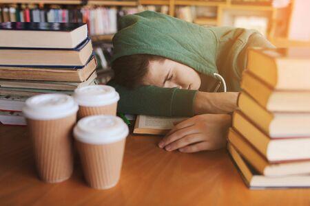 gente durmiendo: las personas, la educación, la sesión, los exámenes y el concepto de la escuela - estudiante cansado o un hombre joven con los libros y dormir de café en la biblioteca Foto de archivo