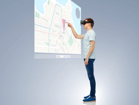 3d technology, virtual reality, entertainment, cyberspace and people concept - happy young man with virtual reality headset or 3d glasses playing game and touching screen with gps navigator map