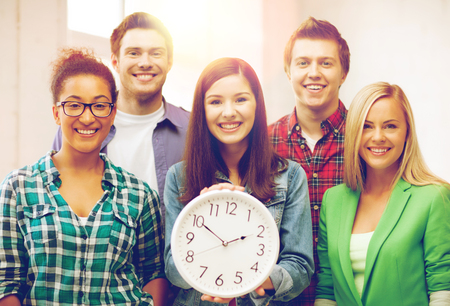people laughing: education concept - group of students at school with clock
