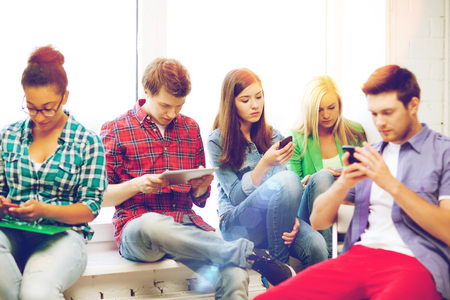internet school: education and internet concept - students looking at their phones and tablet pc at school