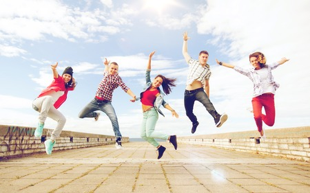 summer, sport, dancing and teenage lifestyle concept - group of teenagers jumping Reklamní fotografie