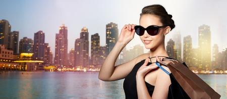 販売、ファッション、人々、高級コンセプト - ドバイの夜街ライト通り背景上のショッピング バッグと黒のサングラスで幸せな美しい若い女