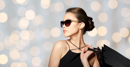 sales person: sale, fashion, people and luxury concept - happy beautiful young woman in black sunglasses with shopping bags over holidays lights background