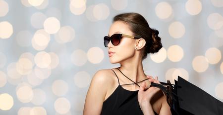 donne eleganti: vendita, la moda, le persone e il concetto di lusso - felice bella giovane donna in occhiali da sole neri con borse della spesa su vacanze lights background