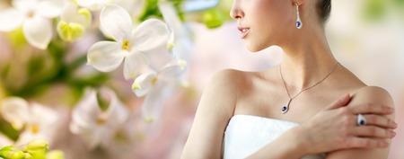 아름다움, 보석, 사람과 고급 개념 - 자연 봄 라일락 꽃 배경 위에 귀걸이, 손가락 반지와 펜던트와 아름 다운 아시아 여자 또는 신부