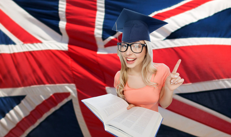 the encyclopedia: people, national education, knowledge and graduation concept - smiling young student woman in mortarboard and eyeglasses with encyclopedia book pointing finger up over english flag