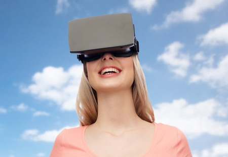 entertainment background: technology, virtual reality, entertainment and people concept - happy young woman with virtual reality headset or 3d glasses over blue sky and clouds background Stock Photo