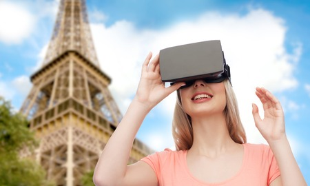technology, virtual reality, entertainment, travel and people concept - happy young woman with virtual reality headset or 3d glasses over eiffel tower background