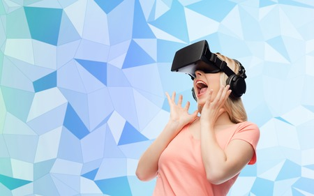 technology, virtual reality, entertainment and people concept - happy young woman with virtual reality headset or 3d glasses and headphones over blue low poly texture background