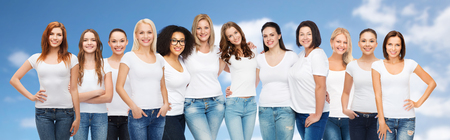 ethnicity: friendship, diversity, body positive and people concept - group of happy women of different age size and ethnicity in white t-shirts hugging over blue sky and clouds background