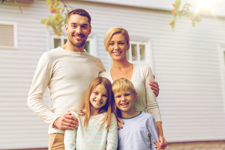 familia, la felicidad, la generación, el hogar y las personas concepto - la familia feliz que se coloca delante de la casa al aire libre