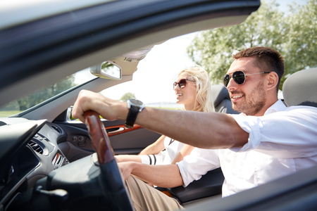 road trip, travel, dating, couple and people concept - happy man and woman driving in cabriolet car outdoors
